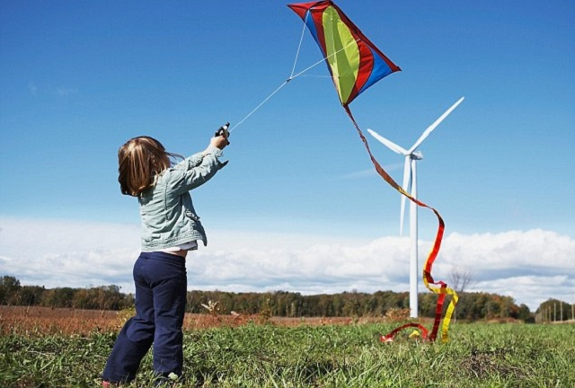 Girl flying kite at wind farm