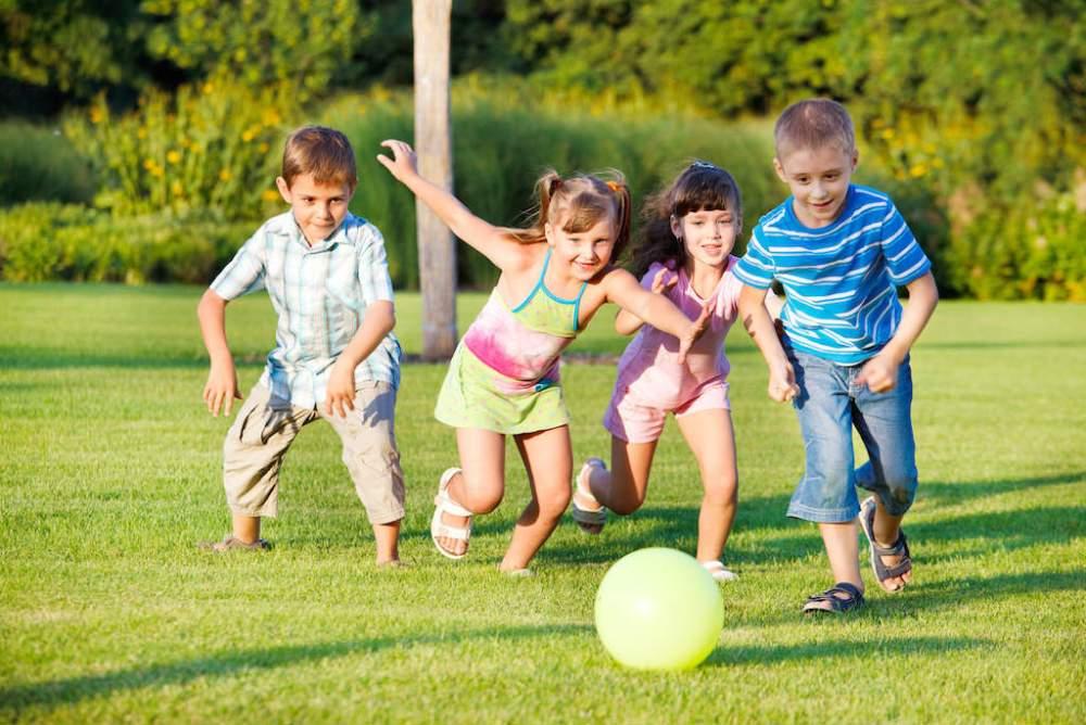 Boys and girls running towards ball
