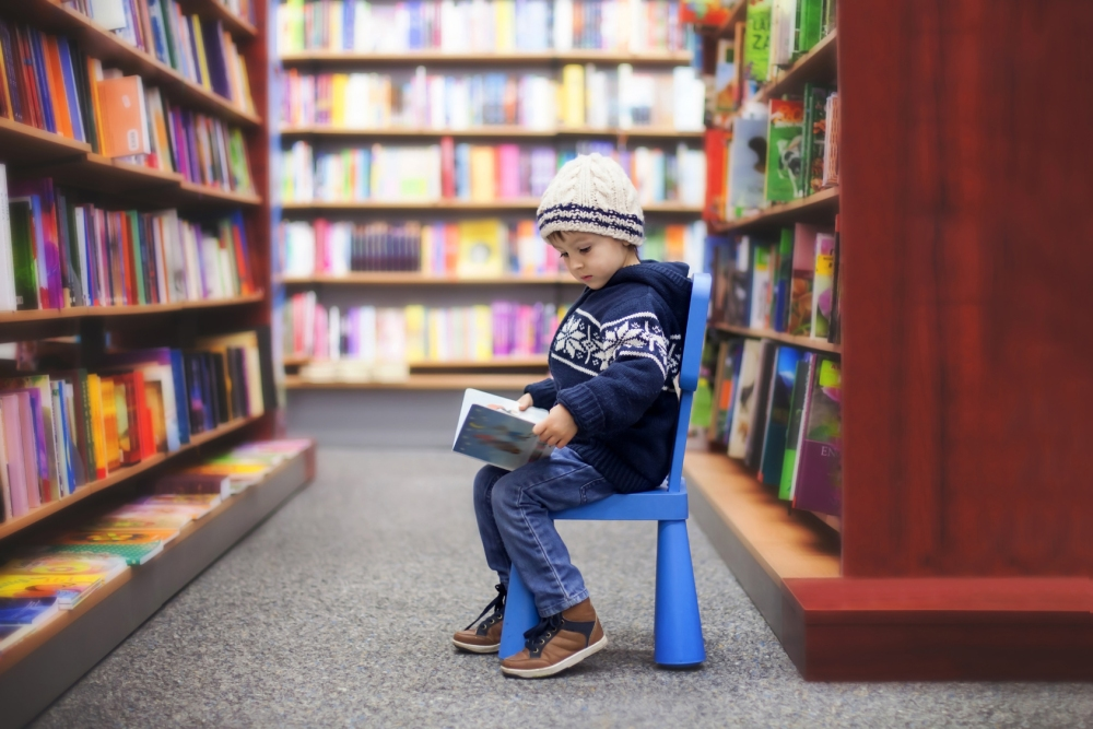 Adorable little boy, sitting in a book store